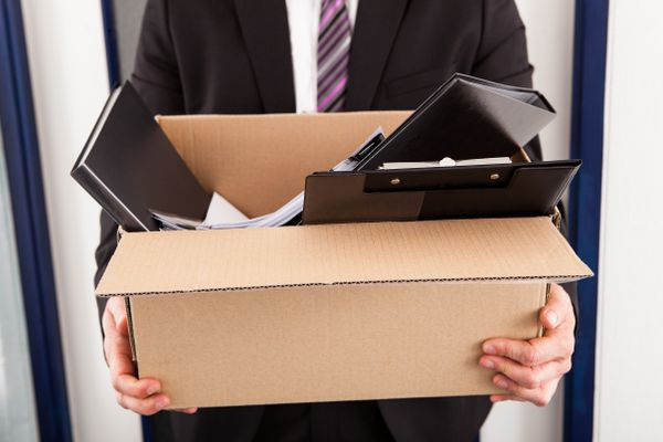 Portrait of young businessman holding a cardboard box in an office. (Thinkstock)