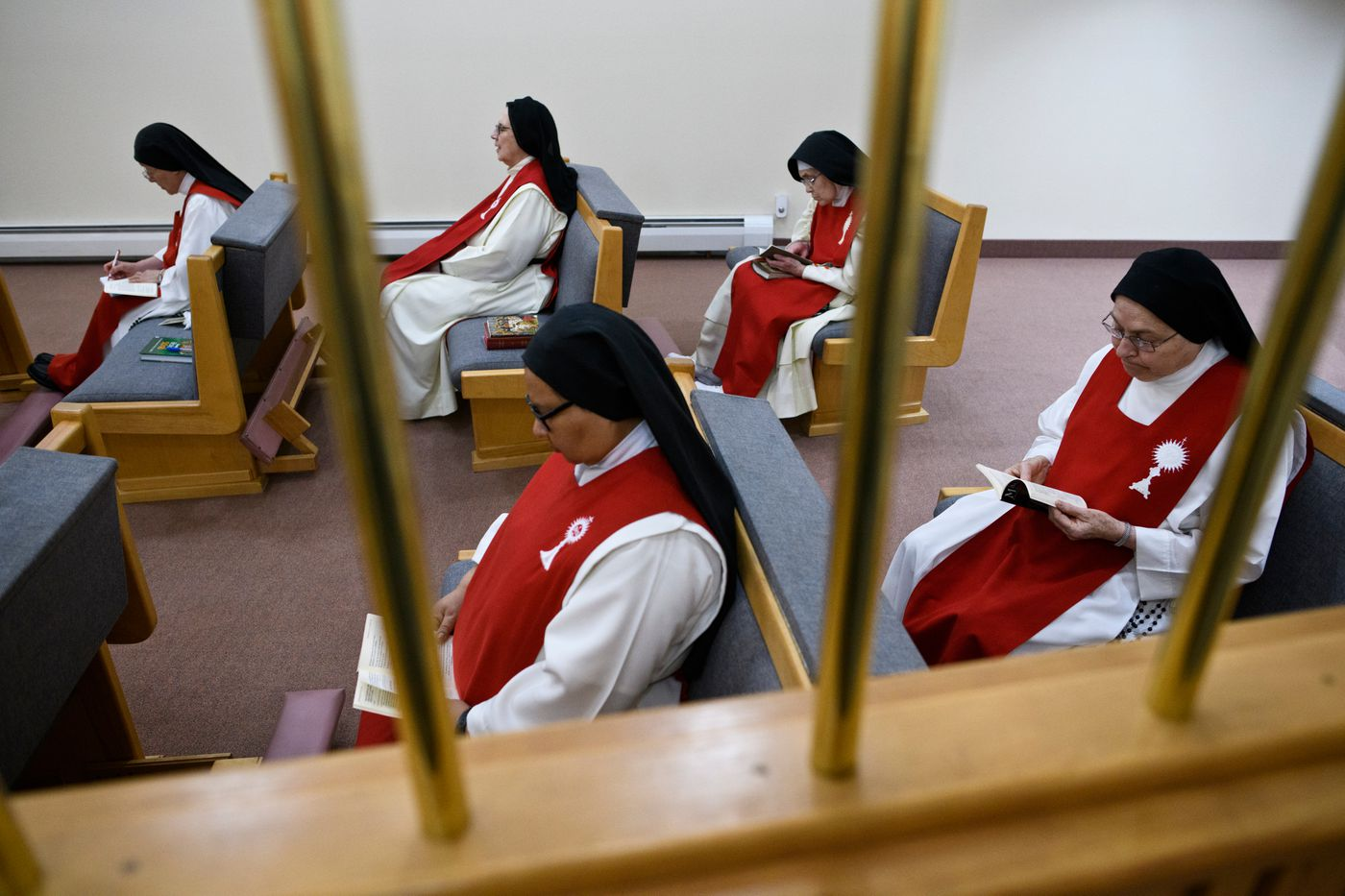 The Sisters of Perpetual Adoration read in an area of their chapel separated from the public portion. (Marc Lester / ADN)