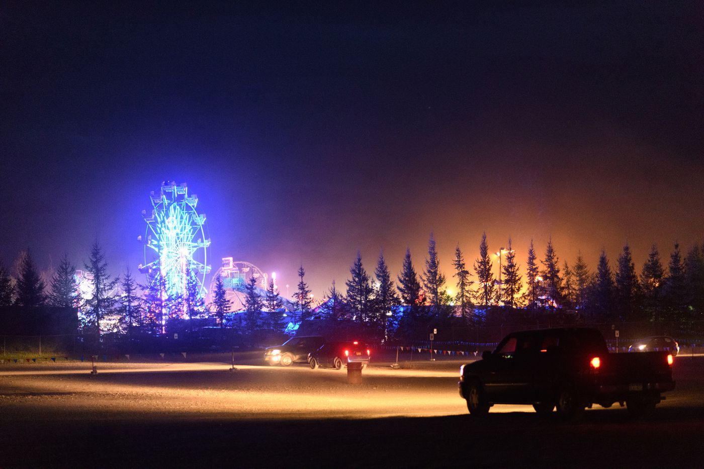 The Alaska State Fair glows after closing time as the parking lot empties. (Marc Lester / ADN)