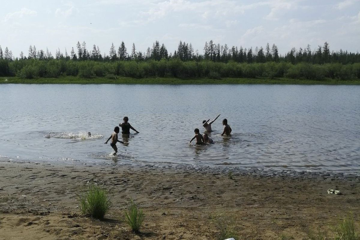 Children play in the Krugloe lake outside Verkhoyansk, the Sakha Republic, about 2900 miles northeast of Moscow, Sunday, June 21, 2020. (Olga Burtseva via AP)