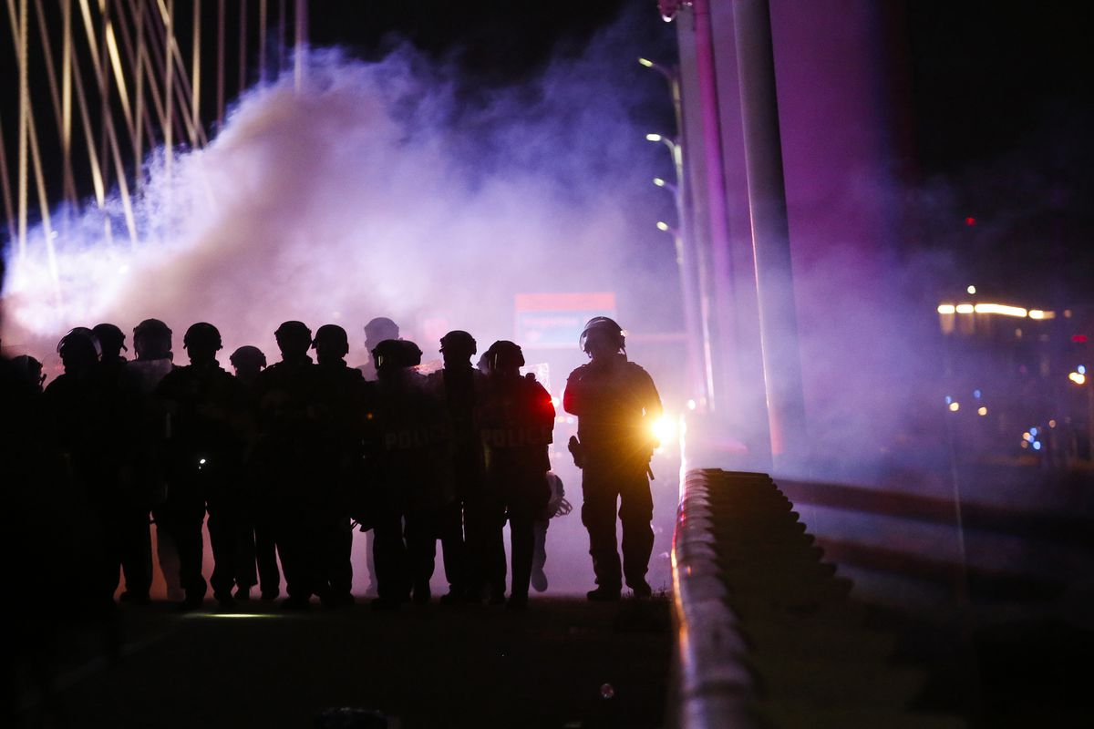 Police deploy smoke bombs and tear gas as they surround protesters who marched onto the Margaret Hunt Hill Bridge while demonstrating against police brutality on Monday, June 1, 2020, in Dallas. The hundreds of protesters were surrounded and detained by police on the bridge and transported to the Dallas County Jail where they were later released. (Ryan Michalesko/The Dallas Morning News via AP)