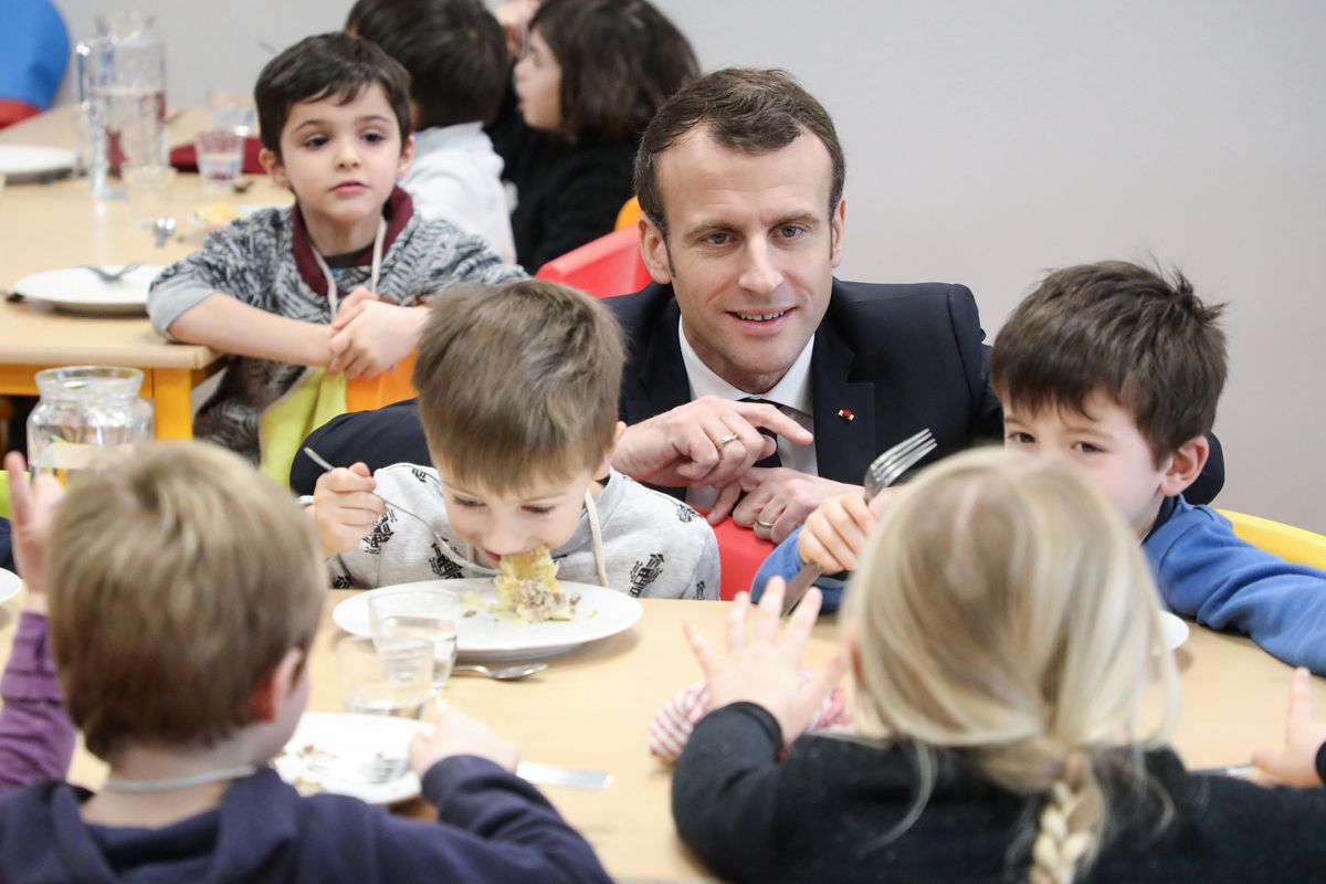 French President Emmanuel Macron meets pupils as he visits a school canteen in Saint-Sozy, southwestern France. By taking meat off the menu at school canteens, the Green Party mayor of Lyon has kicked up a storm of protest. (Ludovic Marin/Pool Photo via AP, FILE)