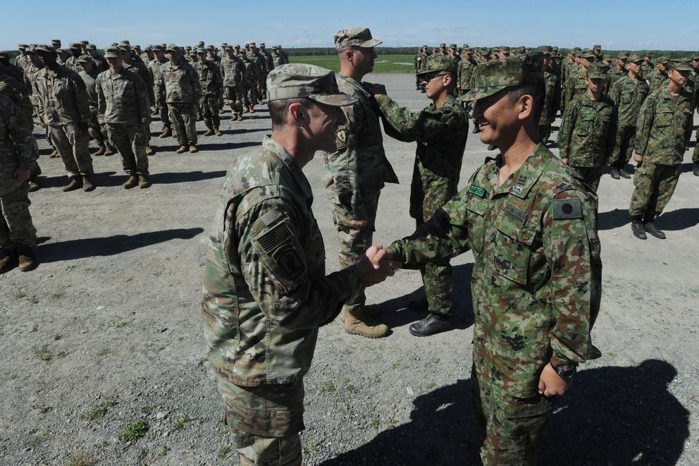 U.S. Army Lt. Col. Matthew Myer commander of the 1st Battalion, 501st Infantry (Airborne) and Lt. Col. Nishiguchi Satoshi commander of the 1st Airborne Battalion, 1st Airborne Brigade, Japanese Ground Self-Defense Force shake hands after exchanging Jump Wings during a bilateral airborne operation at Malemute Drop Zone on JBER, Monday, June 10, 2019. (Bill Roth / ADN)