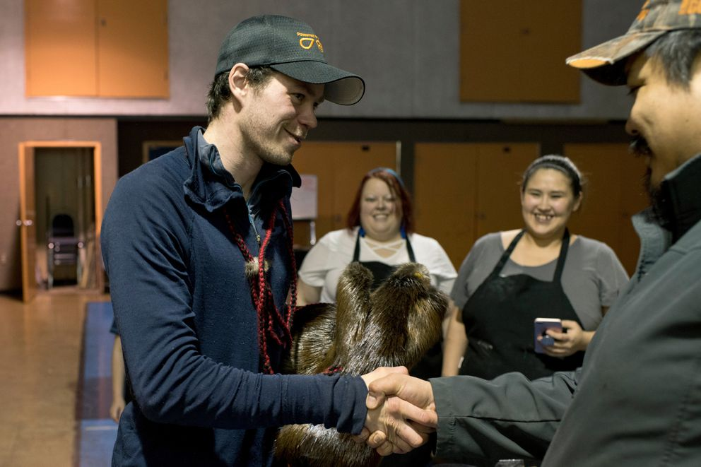 Joar Leifseth Ulsom receives mitts made of beaver fur and moose hide from Daryl Petruska, first chief of the Nikolai Edzeno' Tribal Council, on Tuesday for being the first musher to reach Nikolai. (Marc Lester / ADN)