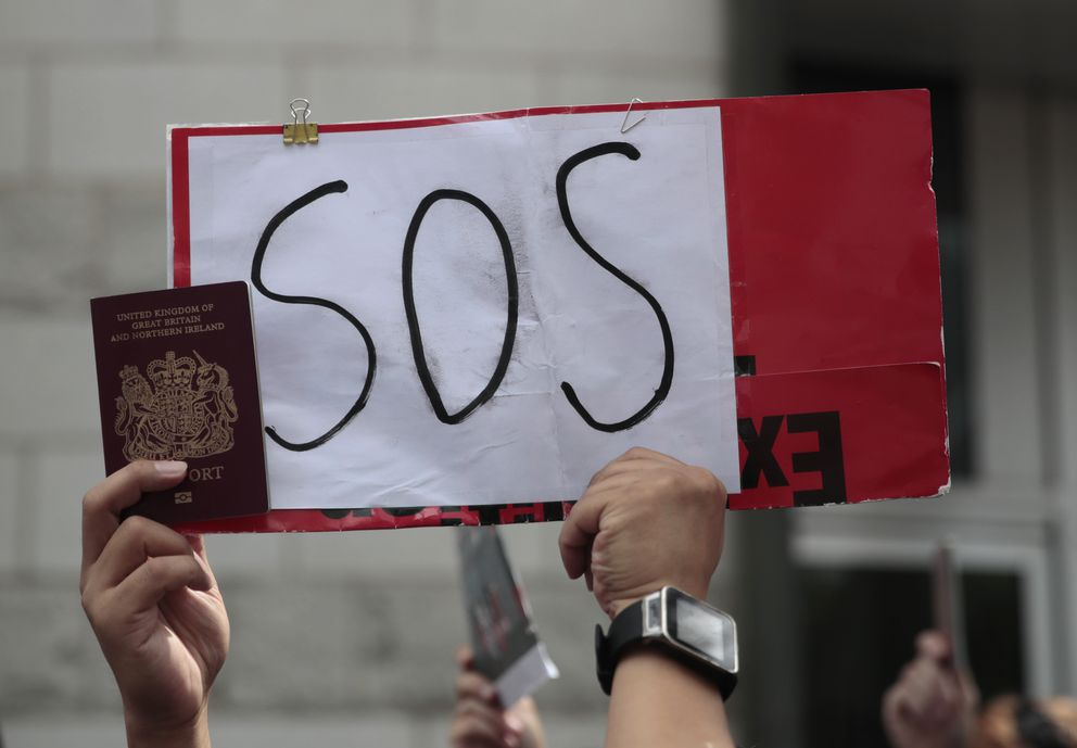 A protestor holds a placard and participates in a peaceful demonstration outside the British Consulate in Hong Kong, Sunday, Sept. 1, 2019. The operator of the express train to Hong Kong's airport has suspended service as pro-democracy protesters gathered there following a day of violent clashes with police. Protesters gathered at the airport after online calls to disrupt travel. (AP Photo/Jae C. Hong)