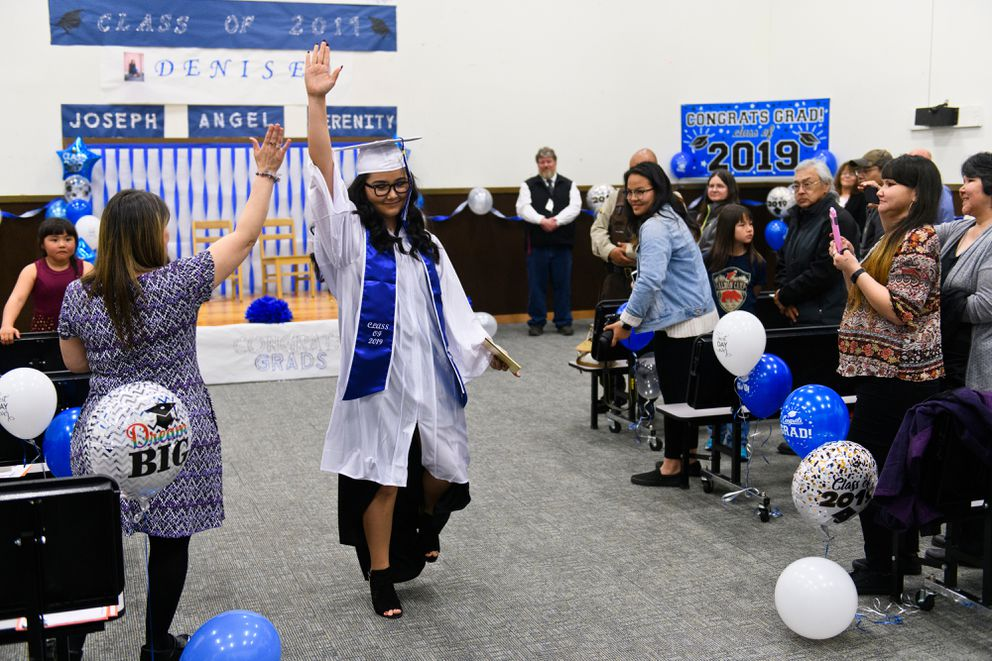 Denise Kalmakoff high-fives teacher's aide Phyllis Amodo at the conclusion of the Akhiok graduation ceremony on May 16, 2019. (Marc Lester / ADN)