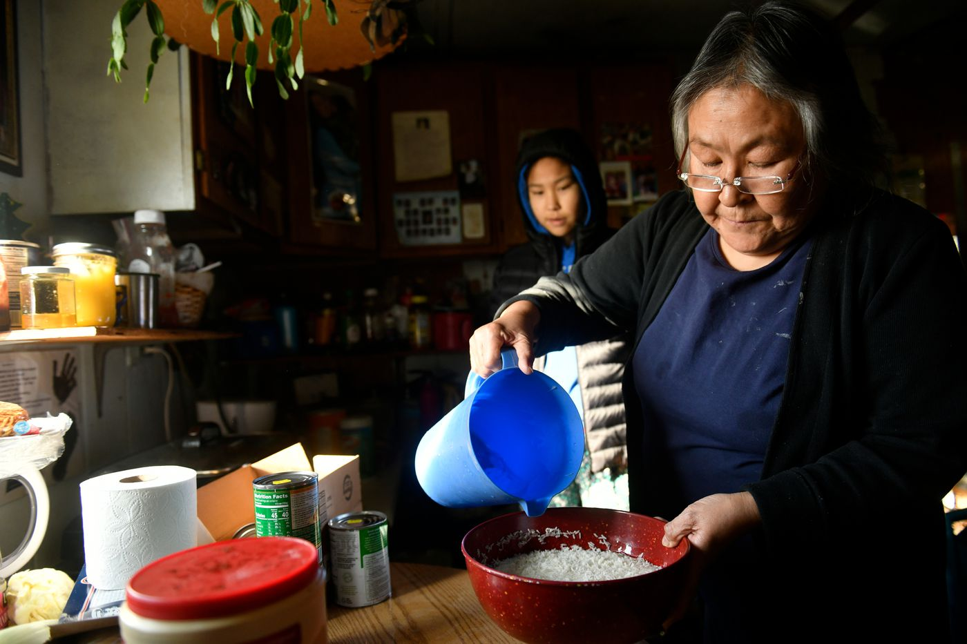 Bernice John, right, prepares a meal in her Newtok home. John said she's looking forward to having more space once she moves to Mertarvik. (Marc Lester / ADN)