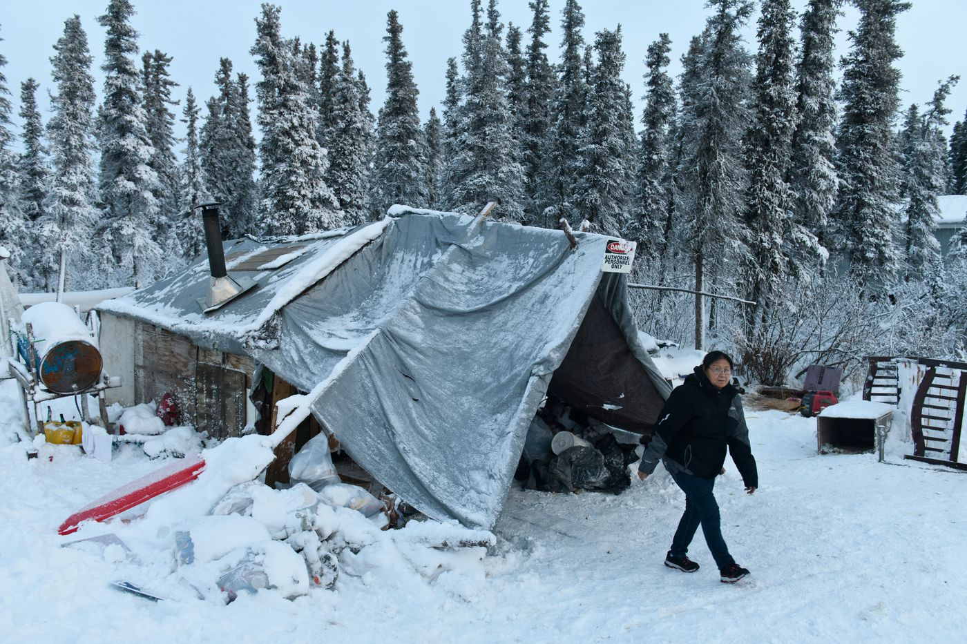 Hannah Coffin walks from her Noorvik home. Six members of the Coffin family currently live in a 12-by-12-foot shelter made of trees, plywood and tarps in Noorvik. After applying for years, they expect to move into a home that is currently under construction in the next couple months. (Marc Lester / ADN)