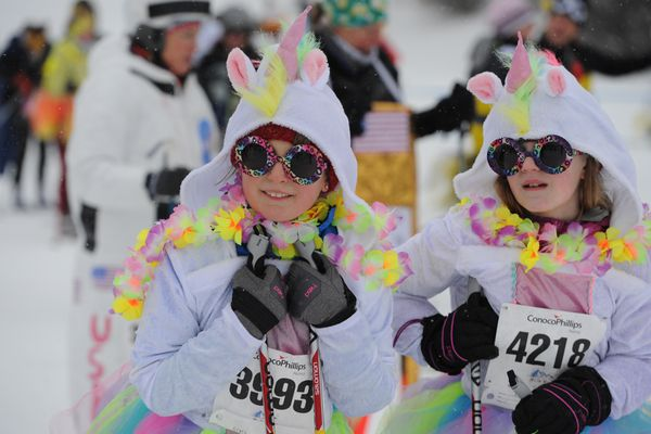Esme Carter, 10 and Megan Fondy, 11, of Team Unicornia prepare to ski in the Party Wave during the 23rd annual Alaska Ski for Women at Kincaid Park on Sunday, Feb. 3, 2019. (Bill Roth / ADN)