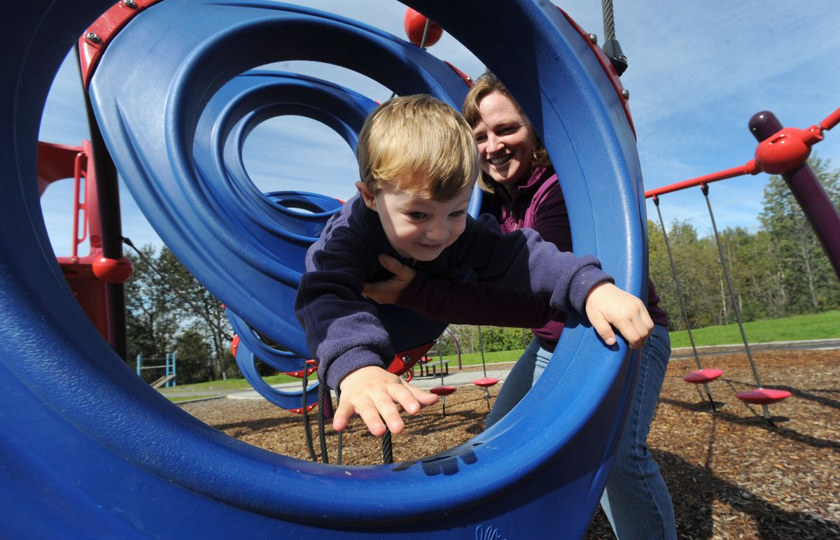 """Colleen Carlson, author of the book """"133 Anchorage Playgrounds,"""" spots her 4-year-old son James as he climbs on playground equipment at Margaret Eagan Sullivan Park near Westchester Lagoon. (Bill Roth / Alaska Dispatch News)"""