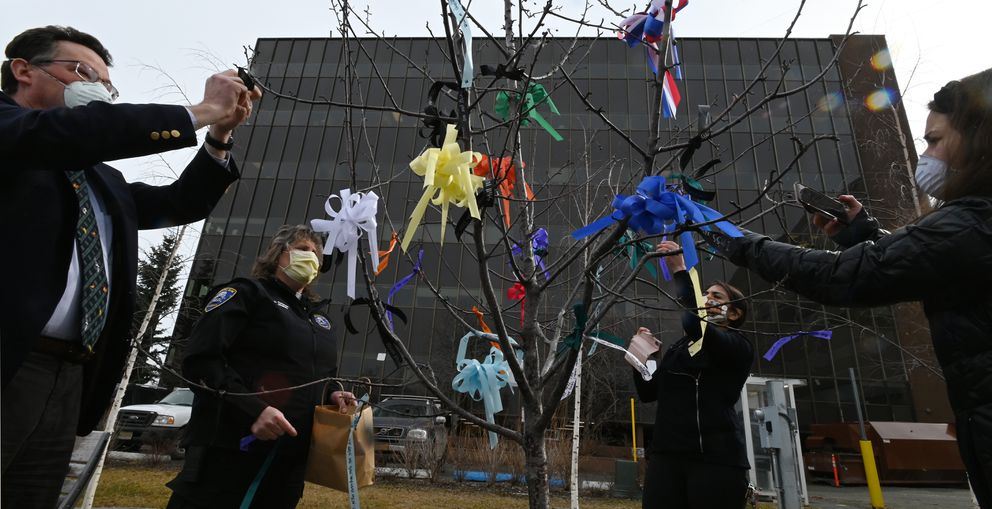 Anchorage District Attorney John Novak, Chaplain Diane Peterson, Stephanie Nayen, and Merissa Pimenta tied ribbons on behalf of victims during the Victims for Justice tree ceremony on Monday. (Bill Roth / ADN)