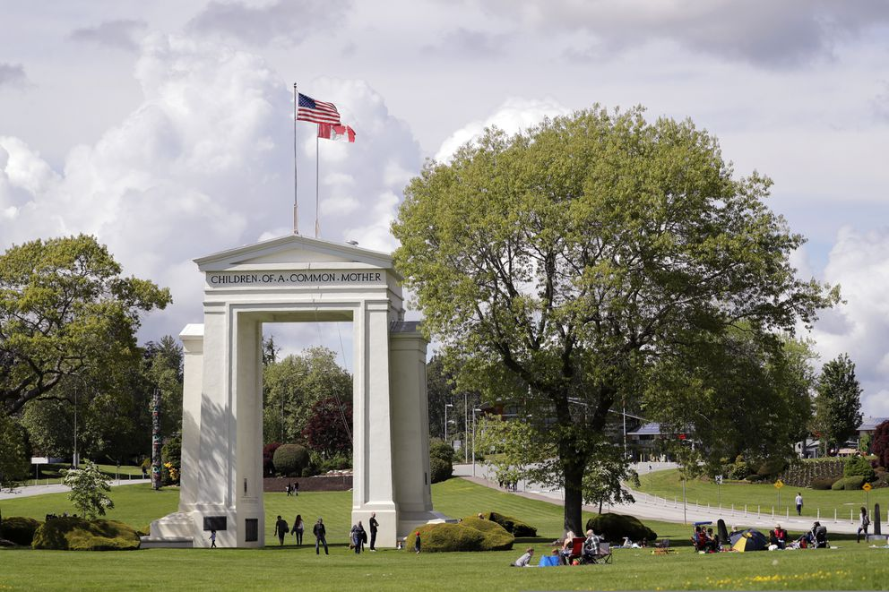 In this photo taken May 17, 2020, people walk back and forth across the border between the U.S. and Canada in Peace Arch Park in Blaine, Wash. (AP Photo/Elaine Thompson)