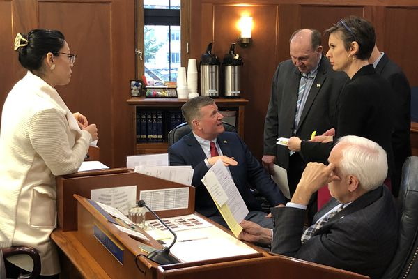 Members of the Alaska House of Representatives gather around Rep. Chuck Kopp, R-Anchorage, as they prepare to vote on the final version of the House's draft state budget Tuesday, March 3, 2020. (James Brooks / ADN)