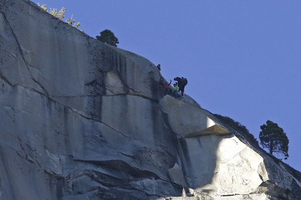 Kevin Jorgeson, bottom left, raises his arms beside Tommy Caldwell after both reached the summit of El Capitan as Kevin Jorgeson, bottom, watches Wednesday, Jan. 14, 2015, as seen from the valley floor in Yosemite National Park, Calif. Caldwell and Jorgeson became the first to free-climb the rock formation's Dawn Wall. They used ropes and safety harnesses to catch them in case of a fall, but relied entirely on their own strength and dexterity to ascend by grasping cracks as thin as razor blades and as small as dimes.