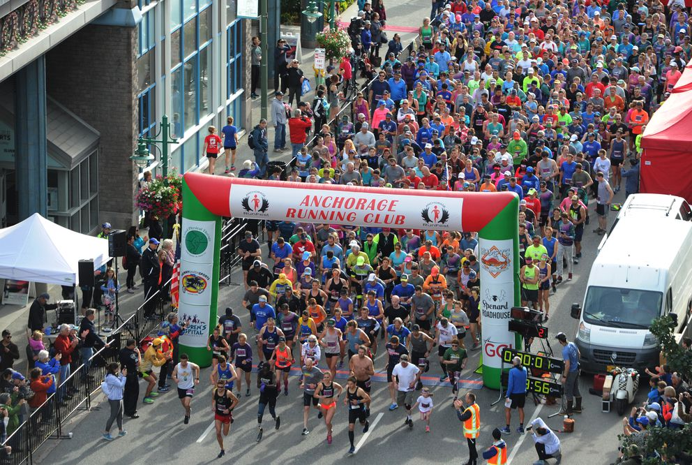 Runners in the half marathon leave the starting line. (Bill Roth / ADN)