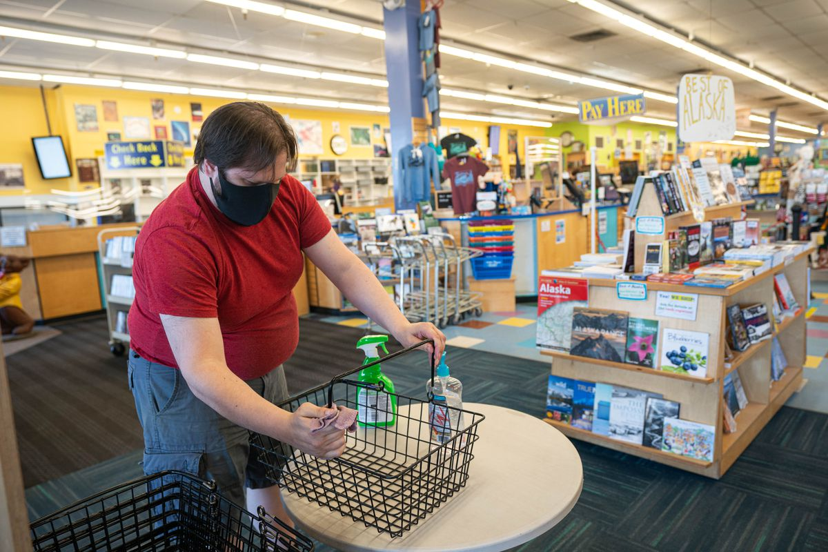 Christian Bailey disinfects shopping baskets at Title Wave Books on May 14 before the store opened to customers. (Loren Holmes / ADN)