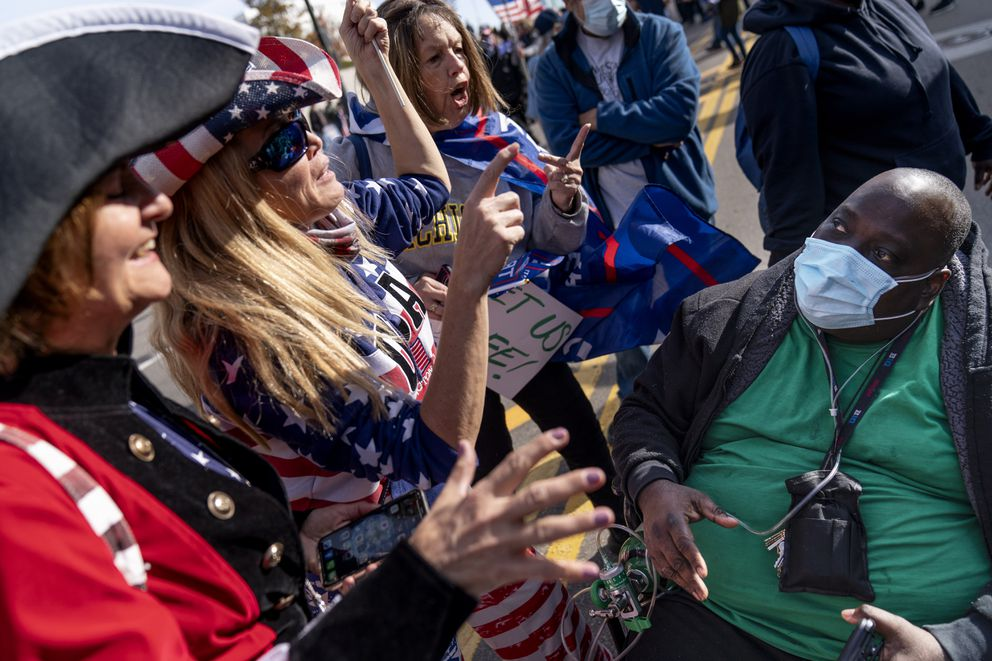 A Biden supporter who would only give his first name, Douglas, right, engages in a debate with Trump supporters demonstrating against the election results outside the central counting board at the TCF Center in Detroit, Friday, Nov. 6, 2020. (AP Photo/David Goldman)