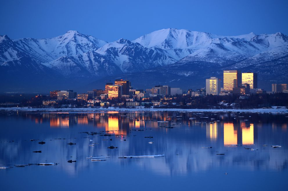 The buildings of downtown Anchorage reflect the color in the sky just after sunset back dropped by the Chugach Mountains and reflected in the calm waters of Knik Arm on Tuesday, April 11, 2017. (Bob Hallinen / Alaska Dispatch News)