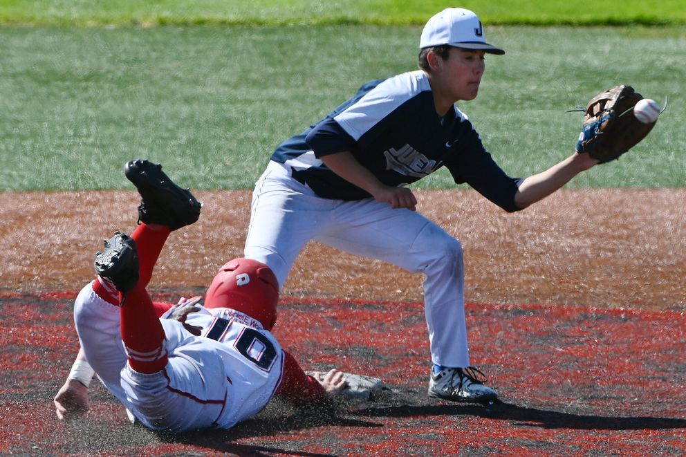 Wasilla's Waylon Payne dives safely back to second base as Juneau's Isaiah Nelson waits for the ball. (Bill Roth / ADN)