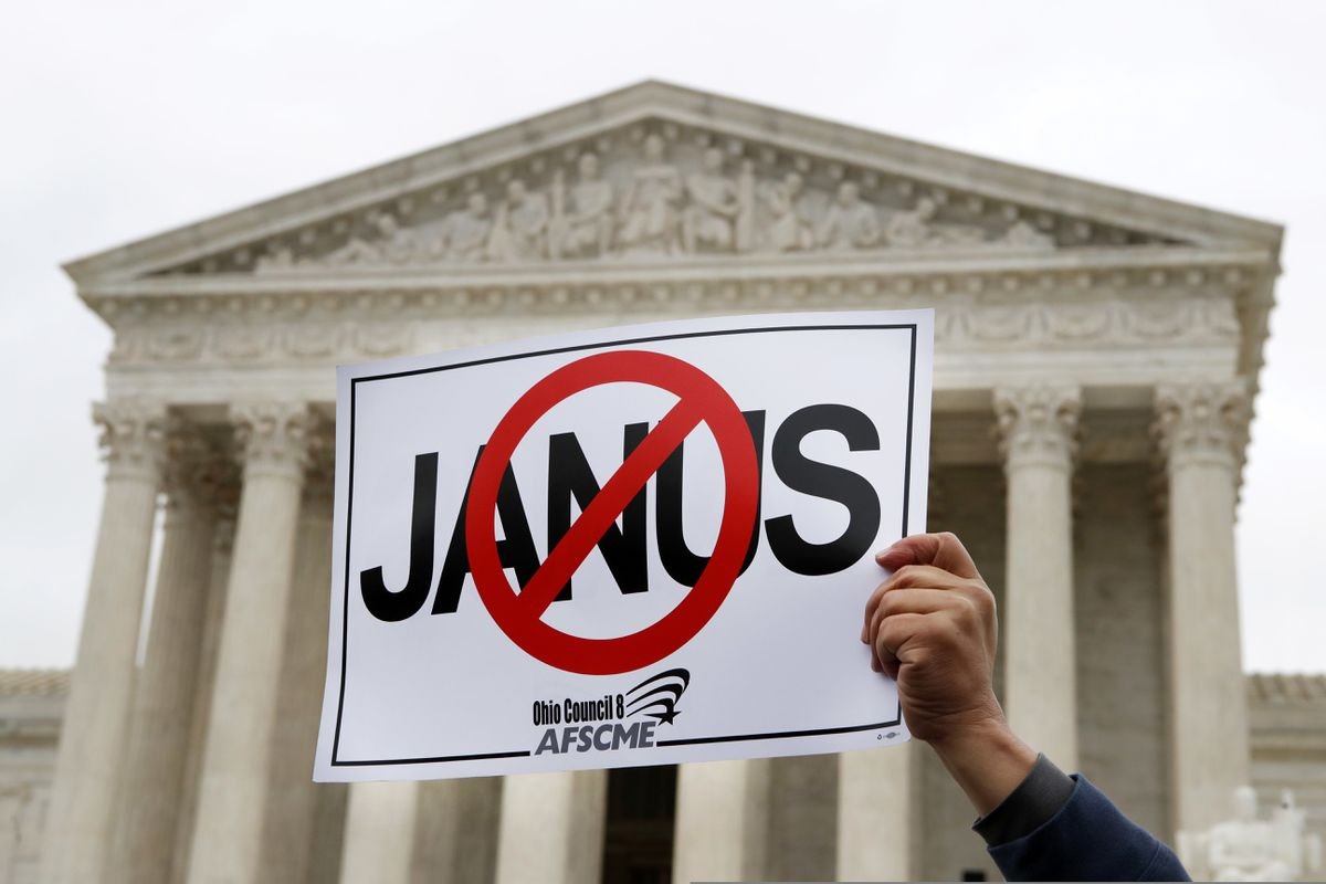 FILE - In this Monday, Feb. 26, 2018, file photo, Stephen Roberts, with the American Federation of State, County and Municipal Employees, holds up a sign against Mark Janus during a rally outside of the Supreme Court, in Washington. Union membership among public employees has fallen only slightly in the nation's most unionized states since the Supreme Court ruled in 2018 that government workers no longer could be required to pay union fees, according to an analysis of federal data conducted for The Associated Press. (AP Photo/Jacquelyn Martin, File)