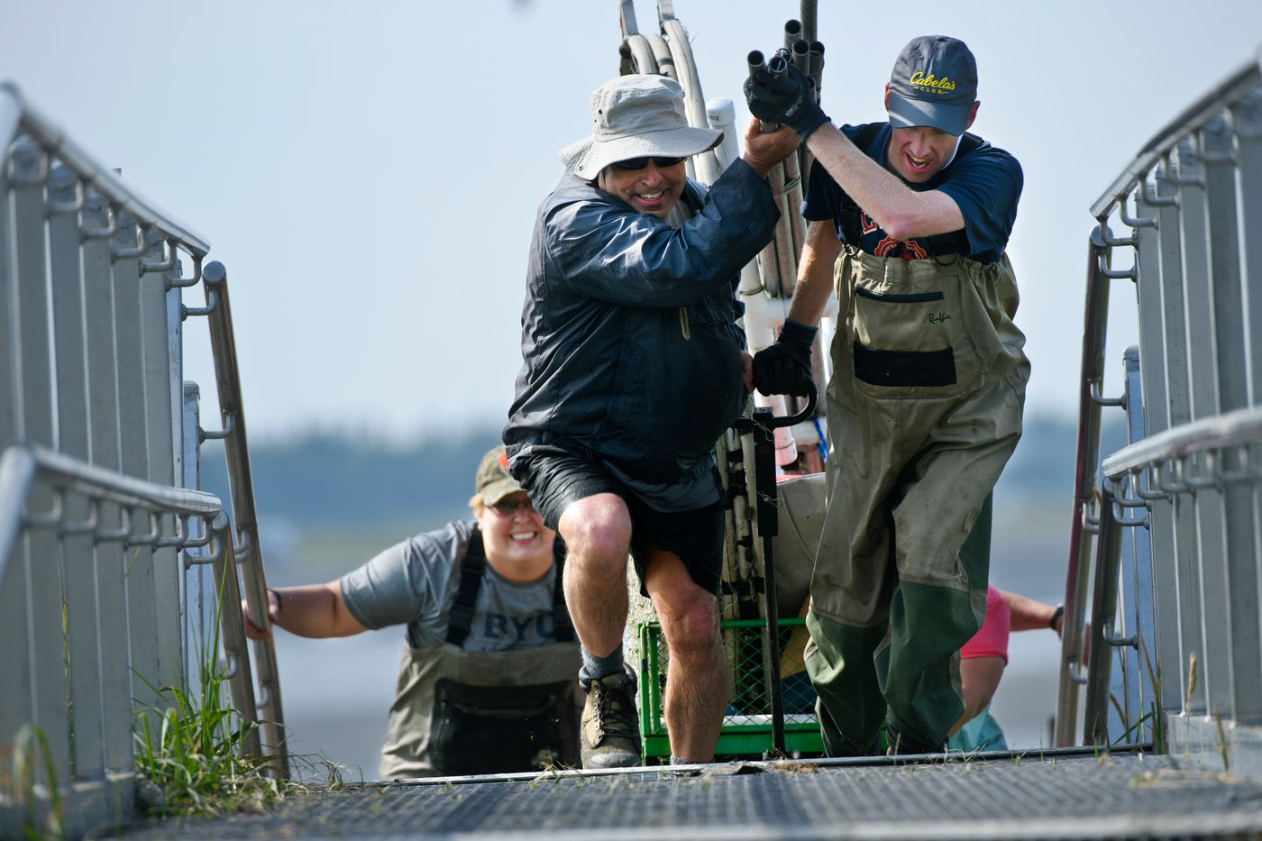 Paul Becker and Tim Platt pull their dipnetting gear on a cart as they leave the Kenai River. (Marc Lester / ADN)