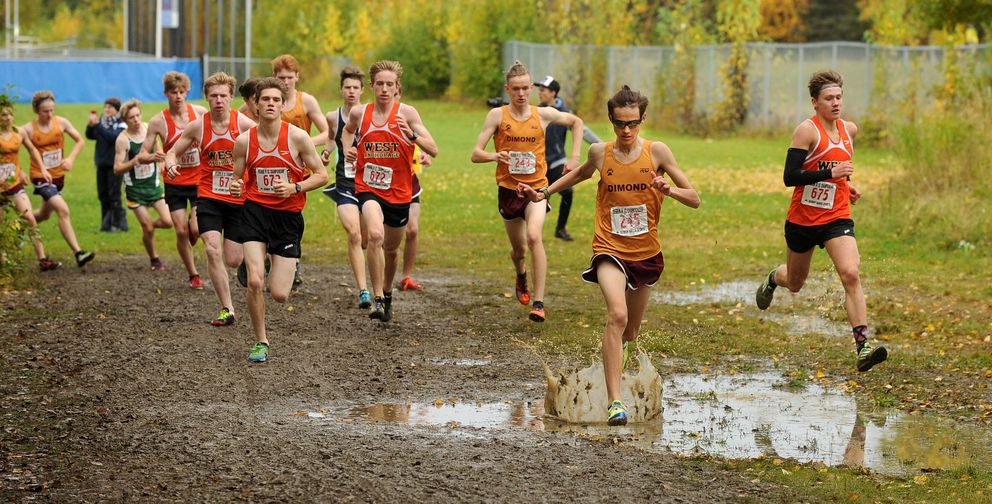 Sonny Prosser splashes through a puddle during the boys' 5K. (Bob Hallinen / Alaska Dispatch News)