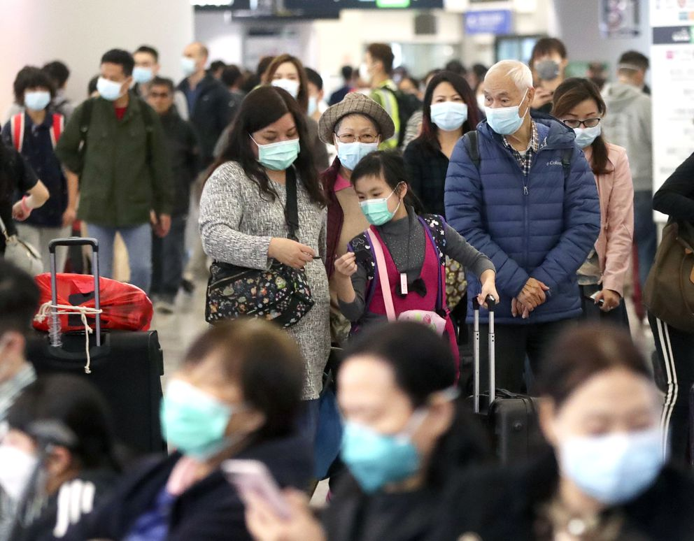 Passengers wearing protective face masks enter the departure hall of a high speed train station in Hong Kong, Friday, Jan. 24, 2020. China expanded its lockdown against the deadly new virus to an unprecedented 36 million people and rushed to build a prefabricated, 1,000-bed hospital for victims Friday as the outbreak cast a pall over Lunar New Year, the country's biggest, most festive holiday..(AP Photo/Achmad Ibrahim)