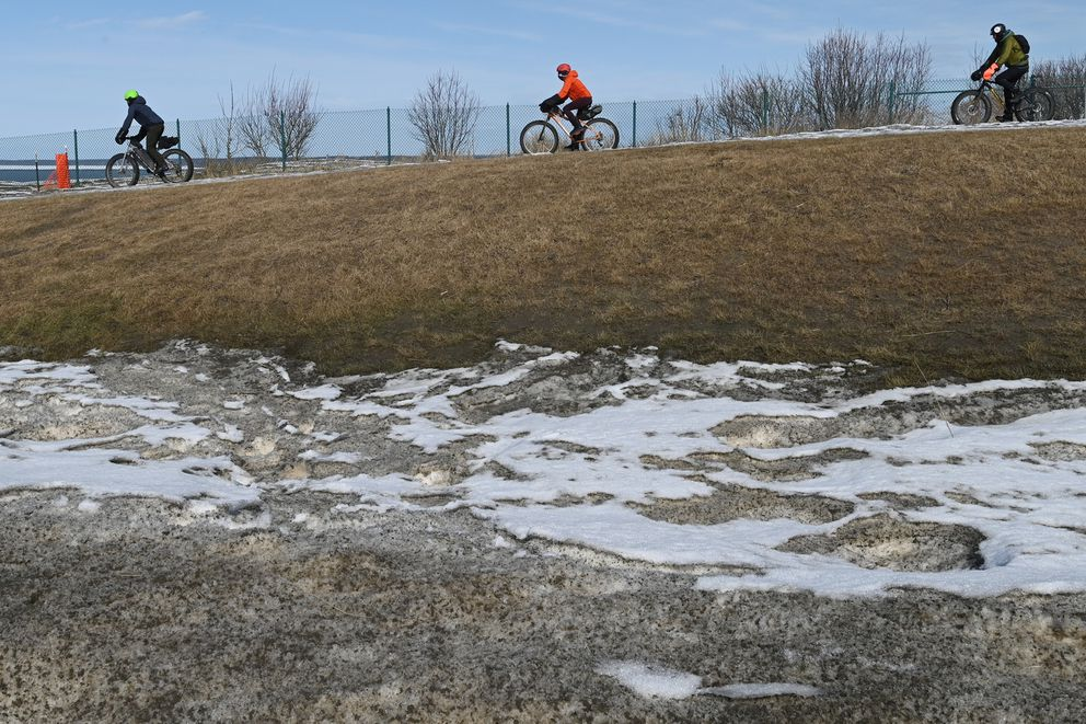 Bicyclists appear to be keeping physical distance as they ride on the Tony Knowles Coastal Trail at Point Woronzof in Anchorage on Sunday, April 5, 2020. (Bill Roth / ADN)