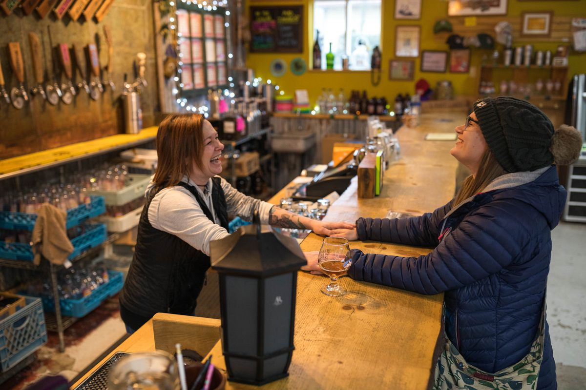 Bartender Diane Million, left, laughs with her friend Kelly Champagne, who came to drink a beer at the Kodiak Island Brewing Company on Thursday, Jan. 24, 2019. Both women's husbands are in the Coast Guard and have been working without pay during the partial government shutdown. Champagne is also a federal contractor who has been furloughed during the shutdown. (Loren Holmes / ADN)