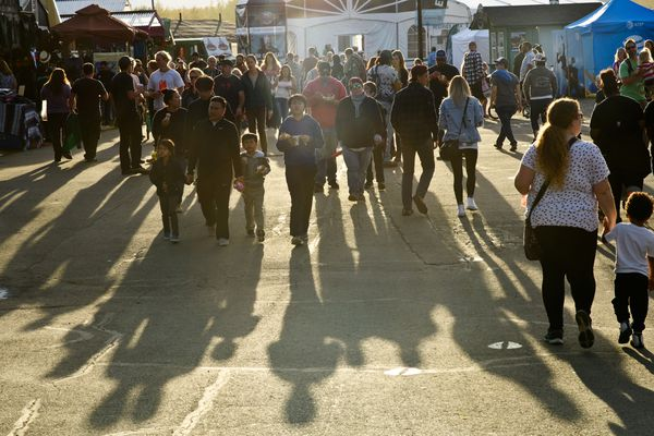 Fairgoers cast long shadows as the sun goes down. (Marc Lester / ADN)