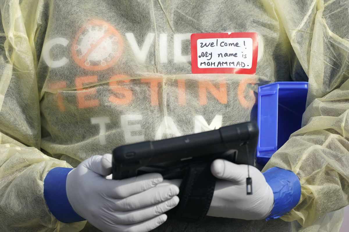 In this Oct. 28, 2020, file photo, a worker wearing gloves, and other PPE holds a tablet computer as he waits to check people at a King County coronavirus testing site in Auburn, Wash., south of Seattle. (AP Photo/Ted S. Warren, File)