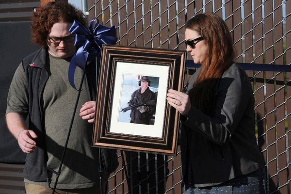 David Smith and sister Amy place a photograph of their late father retired APD Sgt. Ted Smith during a grand opening and naming ceremony for the new tactical training facility for law enforcement in Birchwood. (Bill Roth / ADN)