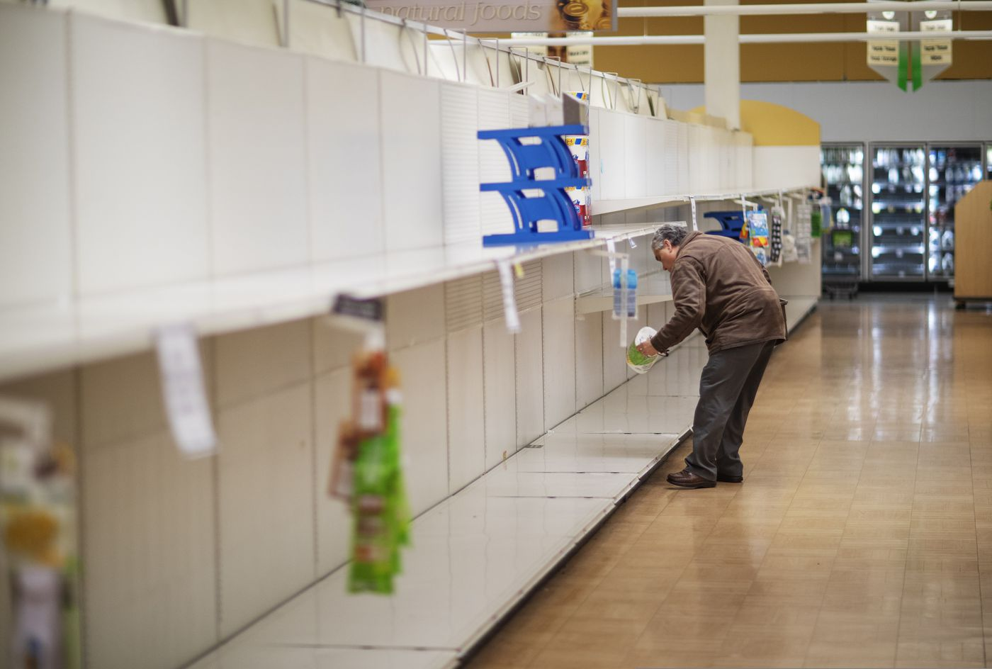 FILE - In this March 19, 2020 file photo, Wade Warner picks up a toilet paper roll at a Stop & Shop supermarket during hours open daily only for seniors in North Providence, R.I. (AP Photo/David Goldman)