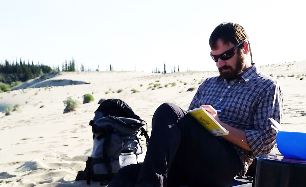 Jeremy Pataky journals in camp in the Great Kobuk Sand Dunes, Kobuk Valley National Park. (Carolyn Kozak)