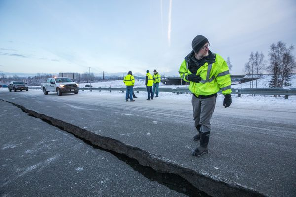 DOT engineer assistant Chris Riekena inspects a crack in the road at the International Airport Road offramp on southbound Minnesota Blvd. Friday, Nov. 30, 2018. A large earthquake caused substantial damage to Southcentral Alaska Friday morning. (Loren Holmes / ADN)