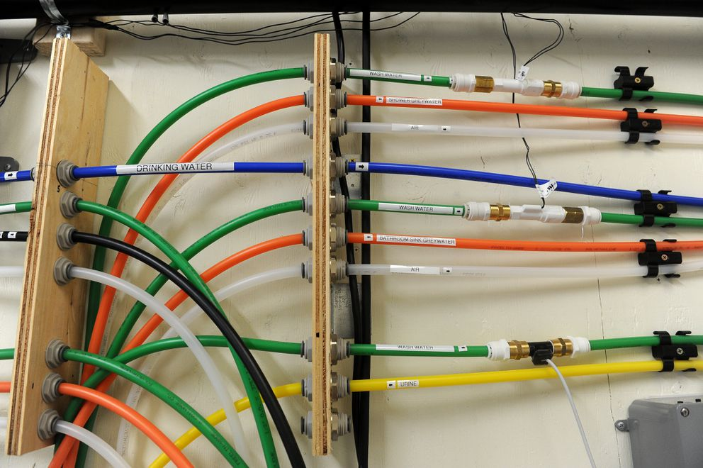 Color-coded water lines are attached to the wall at the in-home water reuse system at UAA on Friday, Aug. 5, 2016, in Anchorage. (Bob Hallinen / Alaska Dispatch News)