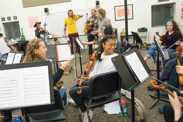 South High junior Elena Kamal talks to her friends in the orchestra before a rehearsal with The Ballroom Thieves Thursday, Sept. 21, 2017. For their Anchorage show, The Ballroom Thieves will be incorporating the talents of the South High School orchestra, which will sit in with the band. (Loren Holmes / Alaska Dispatch News)