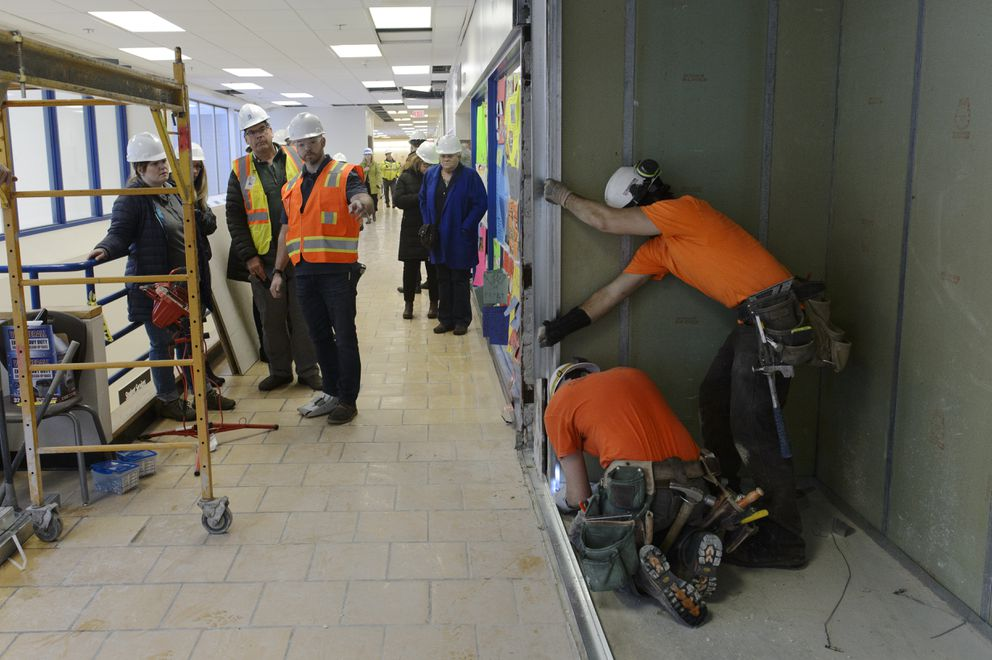 Gabe Shaddy-Farnsworth, top right, and Aren Voss, of Cornerstone Construciton, work on replacing a wall that had collapsed on King Tech High School's second floor. Anchorage School Board members and city officials toured repairs and cleanup underway at King Tech High School on December 7, 2018. Anchorage School District plans to reopen most schools on Monday, December 10, 2018. They have been closed since the magnitude 7.0 earthquake on November 30. (Marc Lester / ADN)