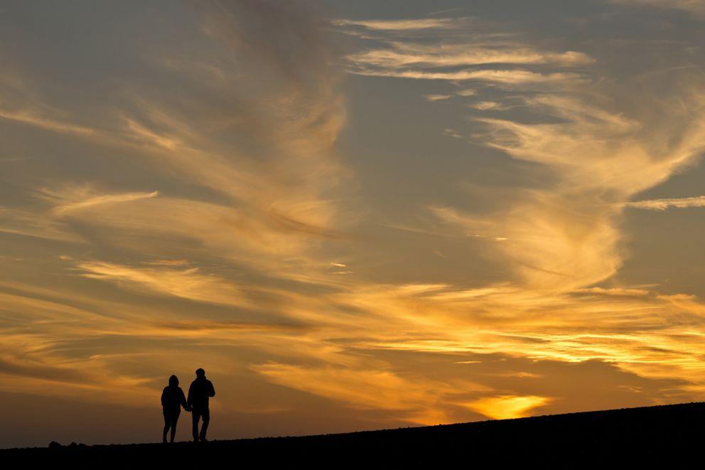 A couple walks on the beach near the tip of the Homer Spit at sunset on Thursday, September 1, 2016. (Marc Lester / Alaska Dispatch News)