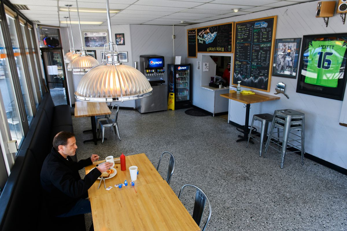 Niels Backers eats at Sandwich Deck restaurant in downtown Anchorage. Tables were separated for dine-in customers on April 27, 2020. (Marc Lester / ADN)