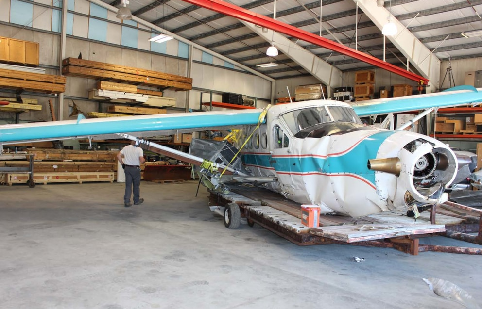 A damaged Taquan Air de Havilland Otter that smashed into Mount Jumbo near Ketchikan, Alaska, in 2018 is shown in a hangar afterward. All aboard survived. (National Transportation Safety Board photo)