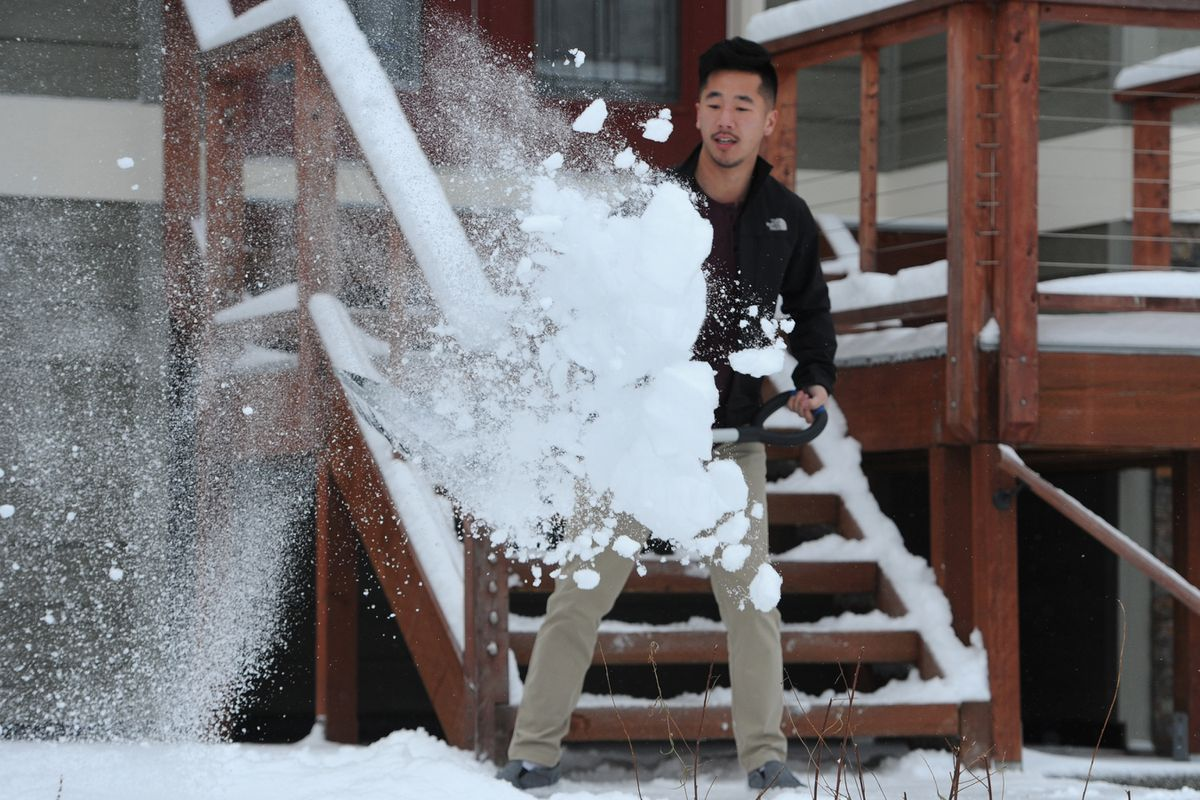 Matt Ha shovels snow at a residence in the Turnagain Heights subdivision on Christmas Day. Ha said he was born and raised in Anchorage and now lives in San Francisco, but is home for the holidays. (Bill Roth / ADN)