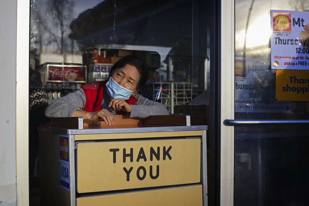 Insook Baik, owner of the Mountain View Shell Gas Station in Anchorage, calls for the next person in line to approach for their free Thanksgiving meal on Thursday, Nov. 26, 2020. (Emily Mesner / ADN)