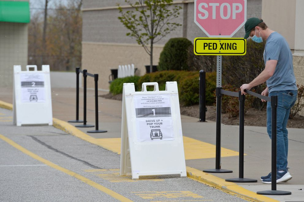 Store manager Michael Henningsen sets up barriers for a drive-through lane at Kohl's in Summit Township, Friday, May 8, 2020, as the Erie region began to reopen Friday from a complete shutdown of non-essential businesses, due to the coronavirus pandemic. Henningsen said he was unsure when his store would open, but some staff was there Friday to begin preparations. (Christopher Millette/Erie Times-News via AP)