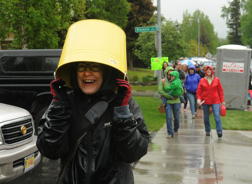 Lisa Shaffer uses the bucket she bought at the Kempton Hills neighborhood garage sale for a rain hat on Saturday, May 21, 2016. Shaffer plans on using her 3-dollar find for a planter on her deck. (Bob Hallinen / Alaska Dispatch News)