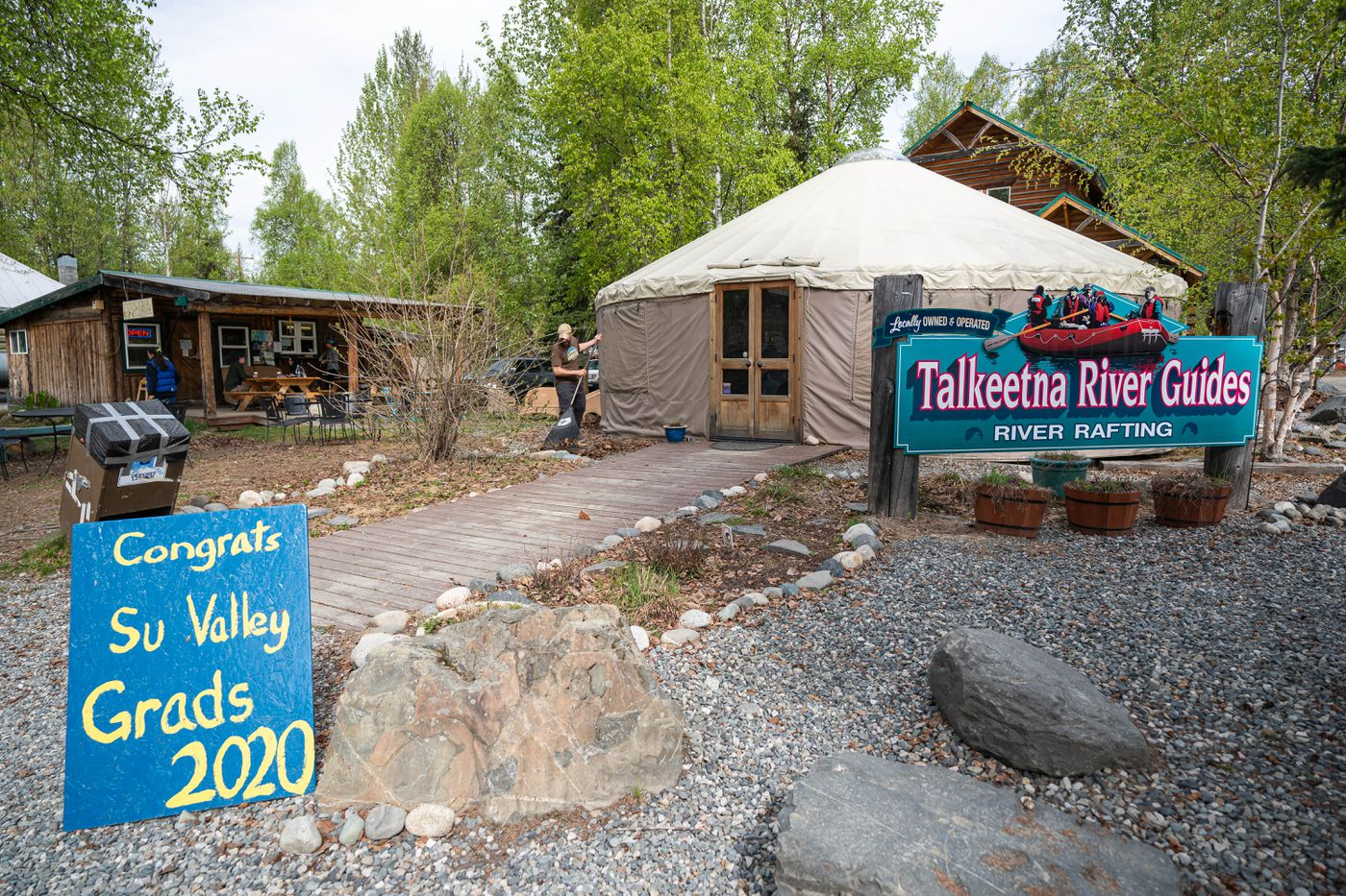 Scott Patridge rakes leaves outside of Talkeetna River Guides on Thursday, May 21, 2020. (Loren Holmes / ADN)
