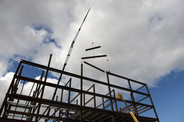 Steel workers assemble the skeleton of the new Kuukpik native village corporation's corporate headquarters on 36th Avenue in Anchorage, AK on Thursday, April 30, 2015. The Nuiqsut village cooperation is located on Alaska's North Slope in the Colville River delta near the Prudhoe Bay oil field. The 60.000 square foot 6 six story structure is being built by Criterion General, Inc. 40,000 square feet of the building is available for lease to other tenants. Commercial real estate developer Pfeffer Development is in charge of the project and KPB Architects is the designer. (Bob Hallinen / ADN)