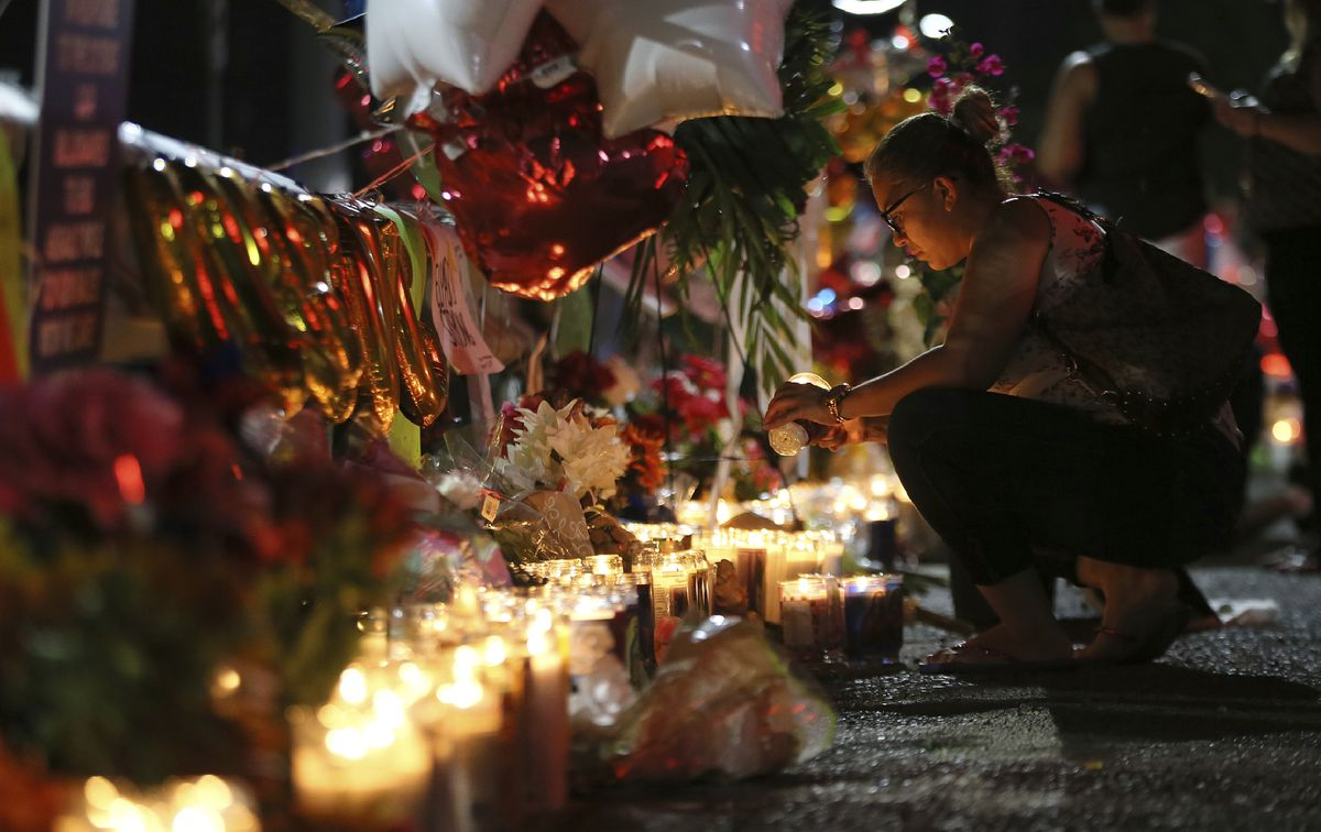 Roxana Jaquez lights a candle at an ever growing memorial Monday, Aug. 5, 2019, outside the Walmart in El Paso, Texas, where a mass shooting took place on Saturday. (Mark Lambie/The El Paso Times via AP)
