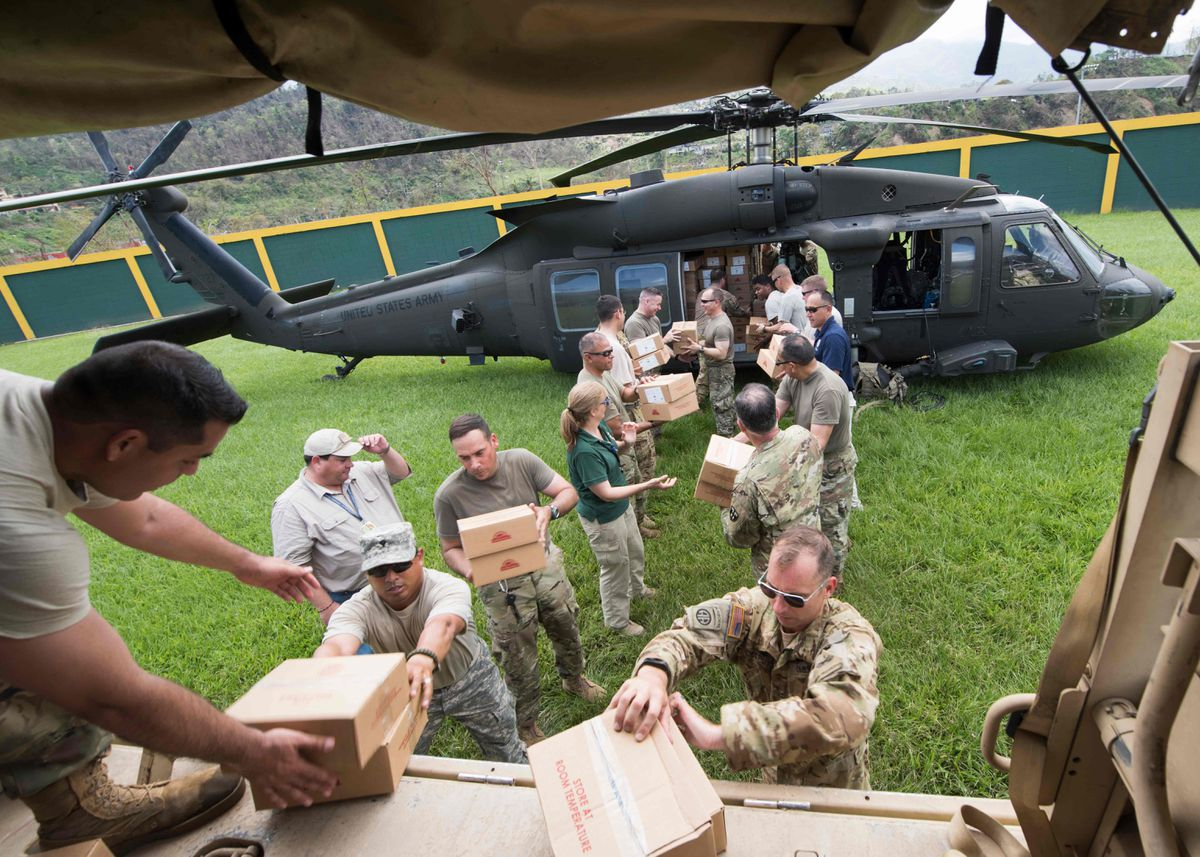 In an image released by the U.S. Department of Defense, U.S. Army Lt. Gen. Jeff Buchanan, the commander of Joint Task Force Puerto Rico, and soldiers from the Puerto Rico National Guard, unload a helicopter carrying relief supplies in Jayuya, Puerto Rico, Oct. 11, 2017. President Donald Trump suggested again on Thursday that Puerto Rico bore some of the blame for its current crisis following twin hurricanes, and that there were limits to how long he would keep troops and federal emergency workers on the island to help. (Department of Defense via The New York Times)