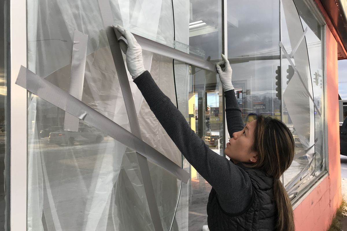 Ami Pyune, owner of Surf Laundry in Anchorage, tapes windows damaged in the earthquake on Friday, Nov. 30, 2018. (Bill Roth / ADN)